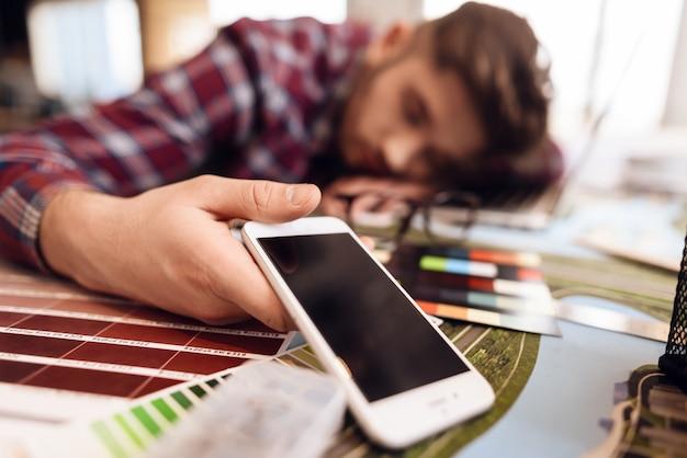 Фрилансер человек спит на ноутбуке, сидя за столом. Premium Фотографии