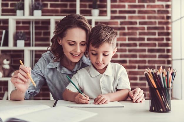 女性と彼女のかわいい幼い息子は絵を描いて笑っています。 Premium写真