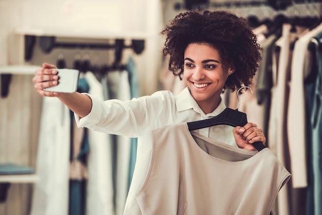 美しいアフロアメリカンの女の子は服を選んでいます。 Premium写真
