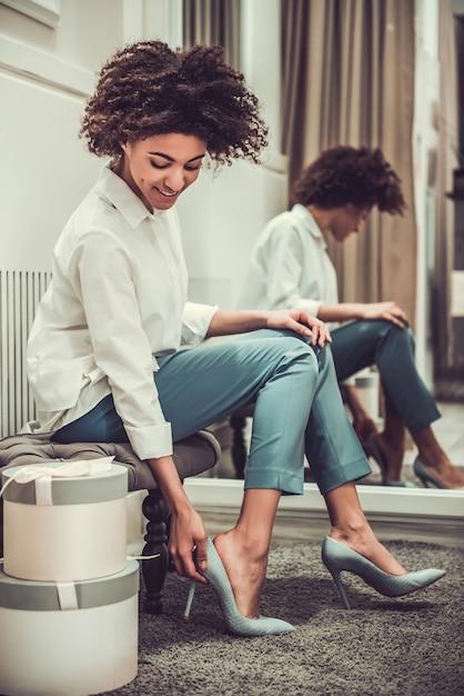 美しいアフロアメリカンの女の子はハイヒールの靴を試着しています。 Premium写真