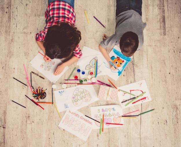 床に横たわっている間描くかわいい子供たちの平面図です。 Premium写真