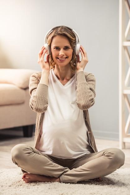 ヘッドフォンで妊娠中の女性は音楽を聴いています。 Premium写真