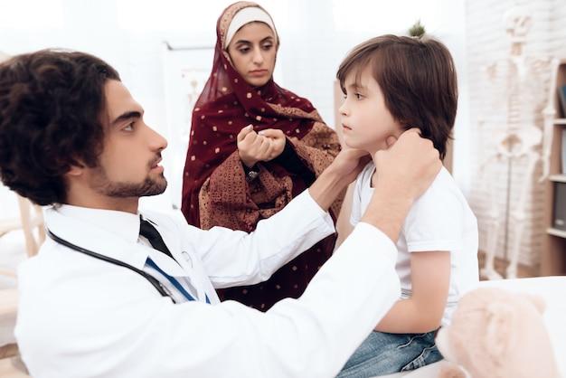 アラブの医者は小さな男の子を診断します。 Premium写真