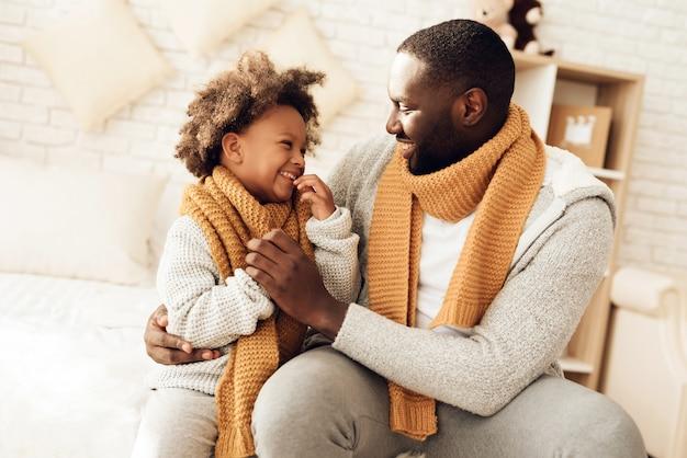 幸せなアメリカ人の父と娘がベッドの上に座って笑っています。 Premium写真