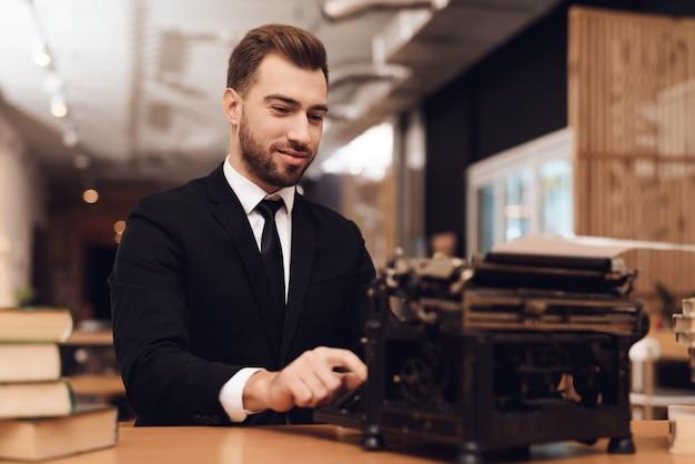 男が古いタイプライターと一緒にテーブルに座っています。 Premium写真