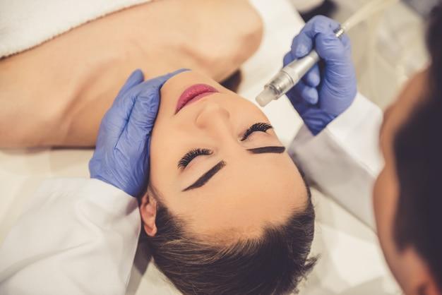 美しい若い女性が顔の皮膚治療を受けています。 Premium写真
