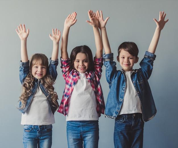 カジュアルな服装で元気な子供たちが手を上げています。 Premium写真