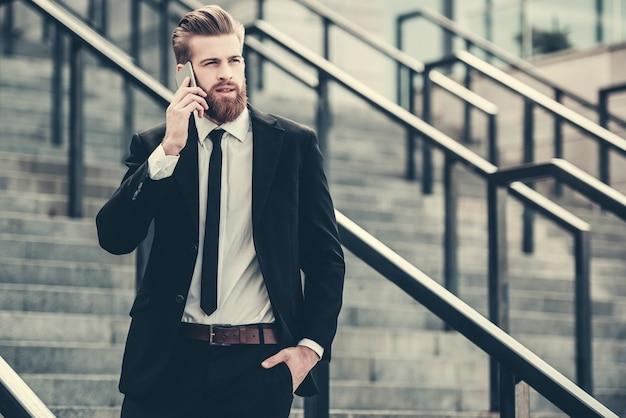 Бизнесмен в классическом костюме разговаривает по мобильному телефону. Premium Фотографии