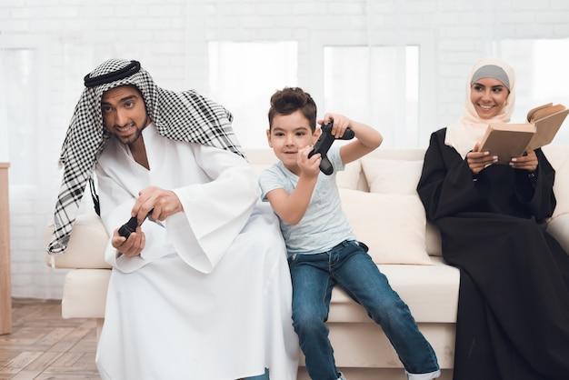 伝統的なアラブの家族がゲーム機を演じています。 Premium写真