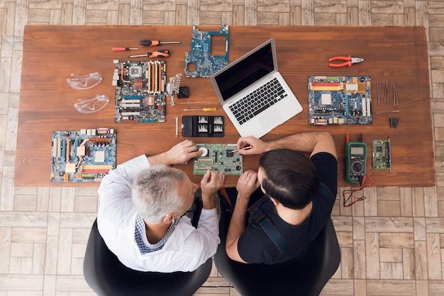 Инженеры осматривают гаджет с помощью стетоскопа. Premium Фотографии