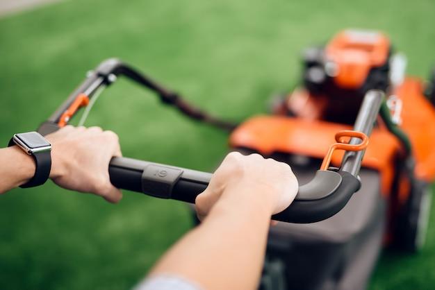 男はハンドルの芝刈り機を持っています。 Premium写真