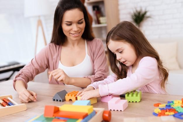 小さな女の子を持つ女性は、木製キューブのロックを構築しています。 Premium写真
