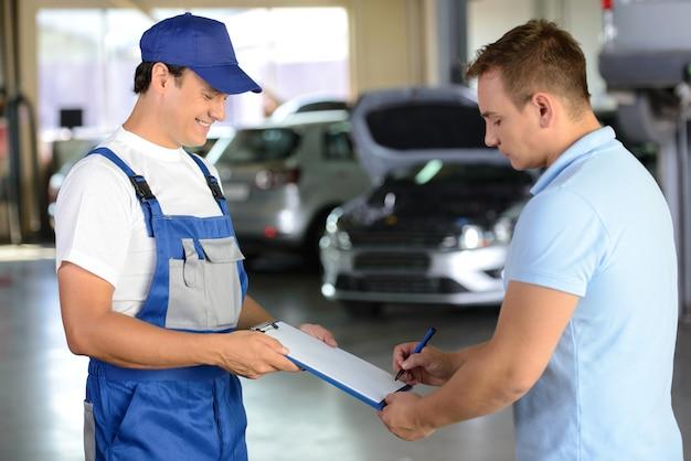 Мужчина дарит клиенту тетрадь с записями выполненных работ. Premium Фотографии