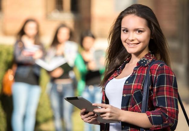 Молодая красивая студентка в колледже, на открытом воздухе. Premium Фотографии