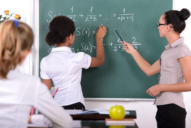 黒板の近くの女の子は数学の方程式を書きます。 Premium写真