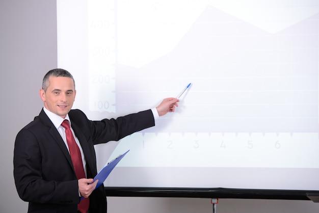 ビジネス会議でスーツを着た男が何かを説明します。 Premium写真