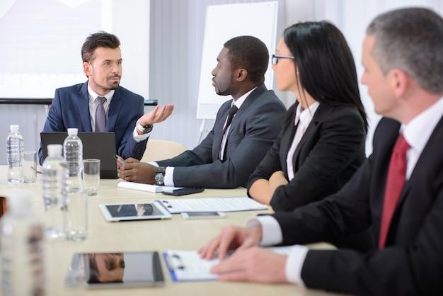 オフィスの会議で正装のビジネス人々。 Premium写真