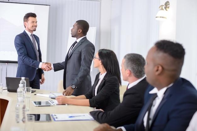 オフィスの会議で握手する人たち。 Premium写真