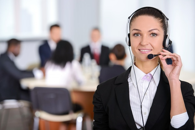 ヘッドセットと笑みを浮かべて女性カスタマーサポートオペレーター。 Premium写真