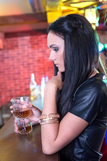 パーティーでは、バーでカクテルを片手に美しい陽気な女の子。 Premium写真