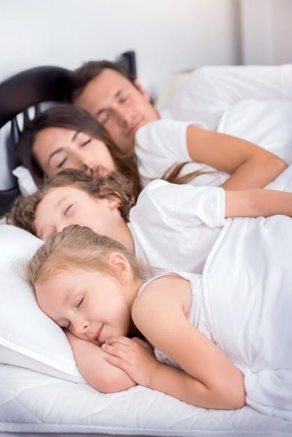 Папа, мама, маленький мальчик и маленькая девочка спят в постели. Premium Фотографии