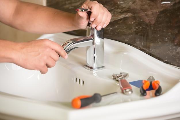 配管工は浴室の水で蛇口を修理しています。 Premium写真