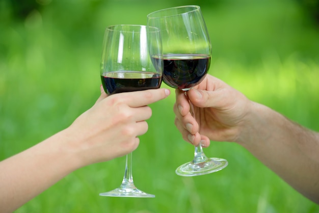 男と女はリラックスして公園でワインを飲みます。 Premium写真