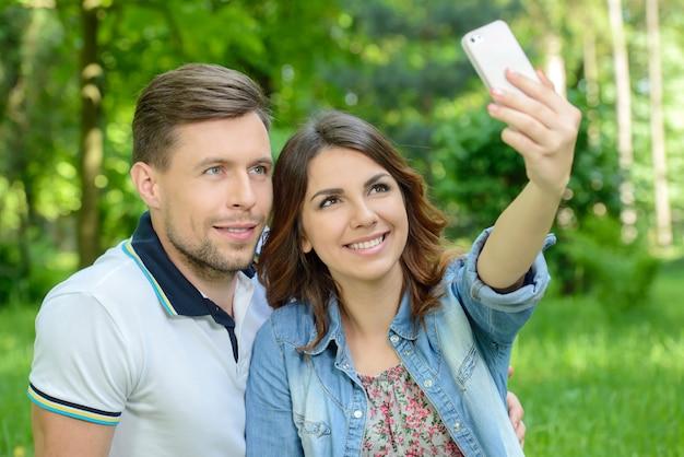 ロマンチックなピクニックの日にスマートフォンで写真を撮るカップル。 Premium写真