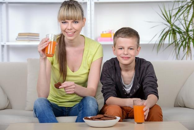 Мать и сын завтракают дома. Premium Фотографии