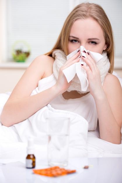 ベッドで風邪に苦しんでいる女性の肖像画。 Premium写真