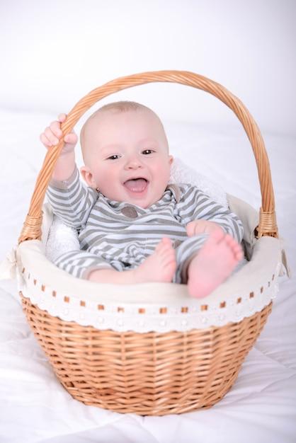 Портрет маленького ребенка в корзине. Premium Фотографии