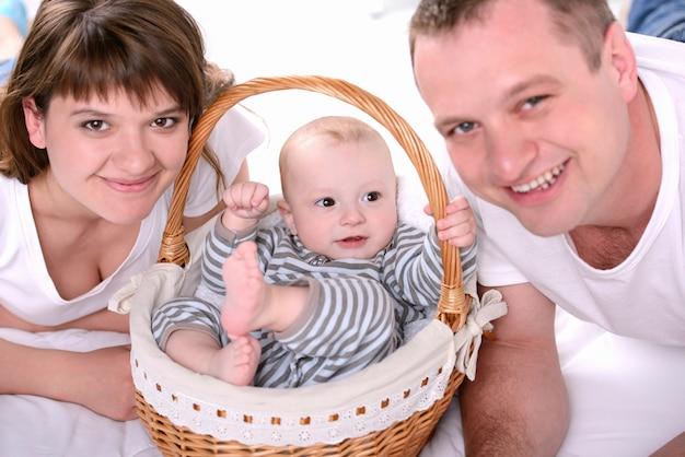 Мама и папа положили маленького ребенка в корзину. Premium Фотографии