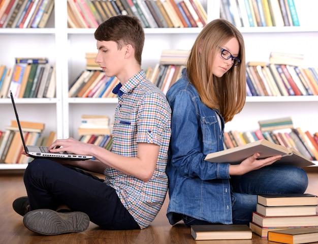 若い学生は本を読んでいるとラップトップを使用しています。 Premium写真