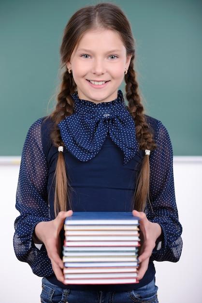 女子高生は彼女の手で本を持っていると笑顔です。 Premium写真