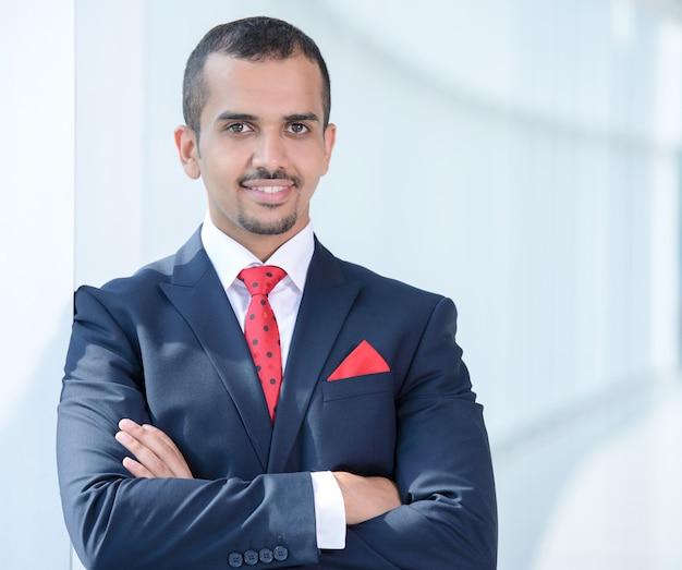 Молодой азиатский бизнесмен стоя в офисе. Premium Фотографии