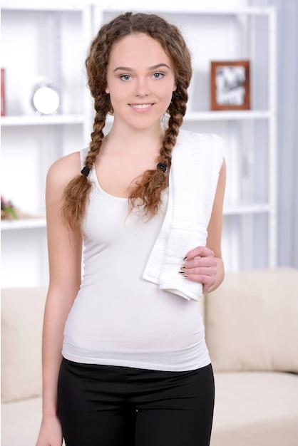 トレーニングの後、彼女の肩にタオルをかざす女性に合います。 Premium写真