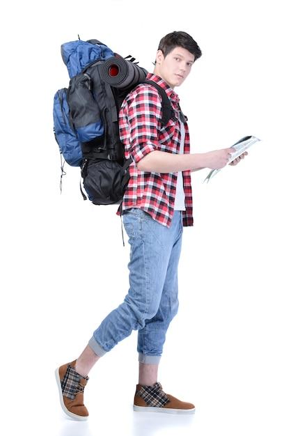 白い壁の上を歩くバックパックを持つ男。 Premium写真