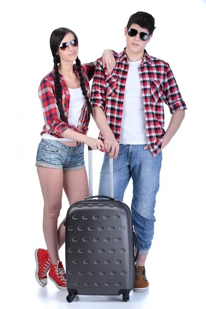 旅行スーツケースを持って歩く若いカップルの完全な長さ。 Premium写真