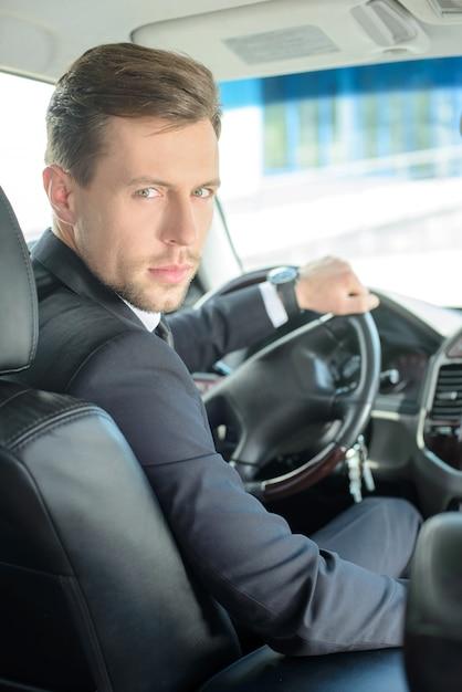 Молодой успешный бизнесмен езда в машине. Premium Фотографии