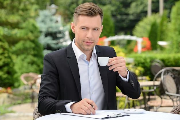 カフェに座ってコーヒーを飲むの実業家。 Premium写真