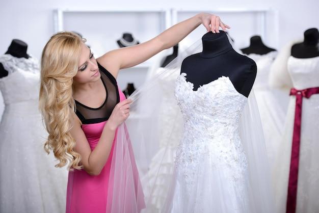 少女は店内のウェディングドレスを見ています。 Premium写真