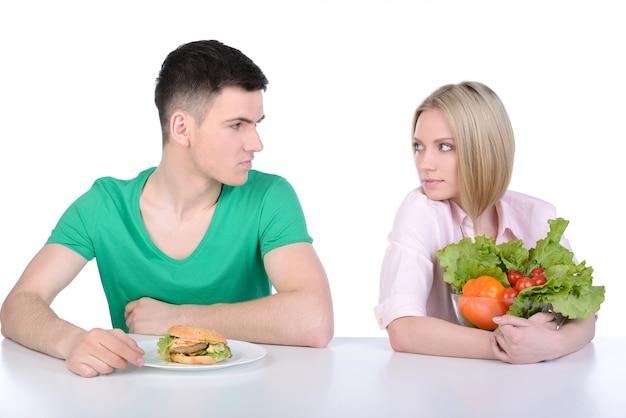 若い男と女がファーストフードを食べる。 Premium写真