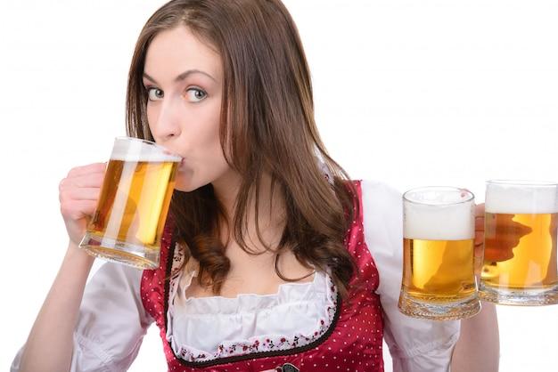 ビールのグラスと民族衣装のセクシーな女の子。 Premium写真