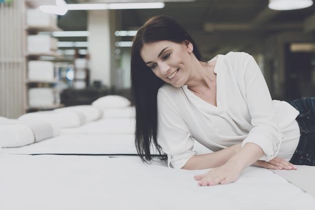 若い女性は店でマットレスを選択します。 Premium写真