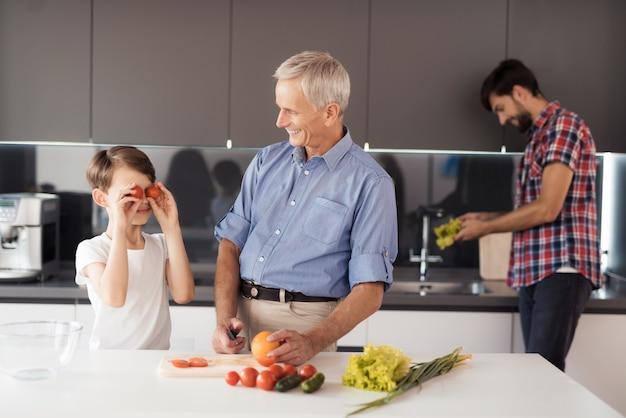 青いシャツを着た老人はサラダを準備しています。 Premium写真