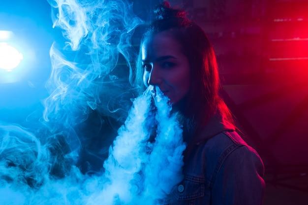 女の子はタバコを吸って、ナイトクラブで煙を出します。 Premium写真