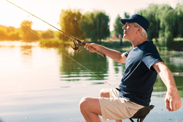 Старик с седыми волосами, рыбалка на реке летом. Premium Фотографии