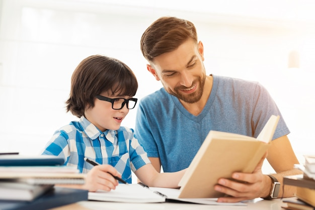 Отец помогает сыну делать уроки в школе. Premium Фотографии