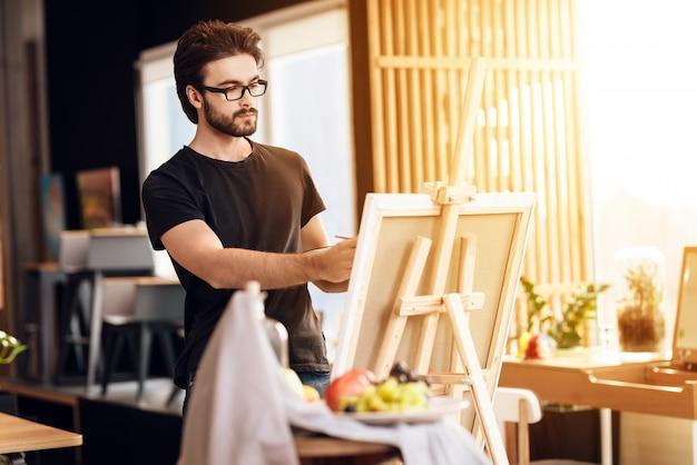 画家のコンセプトです。イーゼルの静物画の男絵。 Premium写真
