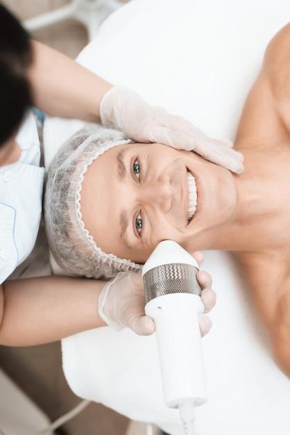 医者は、現代の光脱毛器で男性の皮膚を治療します。 Premium写真